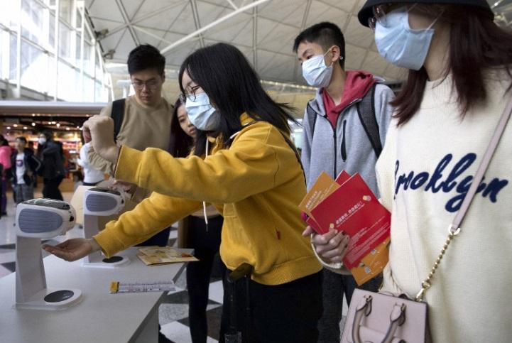 Photo (AP Photo/Ng Han Guan via Mainichi Japan) : Des passagers portant des masques à l'aéroport de Hong-Kong, le 21 janvier 2020.